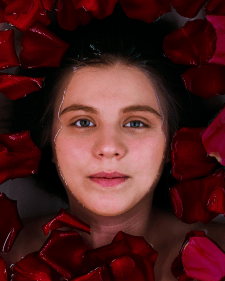 Девушка в воде и лепестках роз